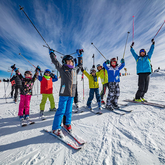 Jubilant group of children and their instructor holding skiis in the air on Mt Hotham