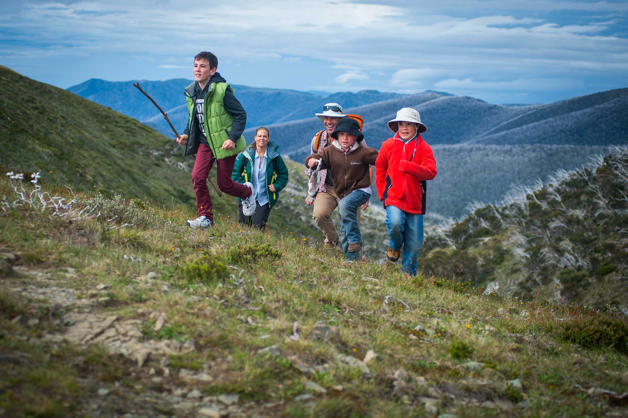 Children and their parents running up a hill on Mt Hotham in the Autumn