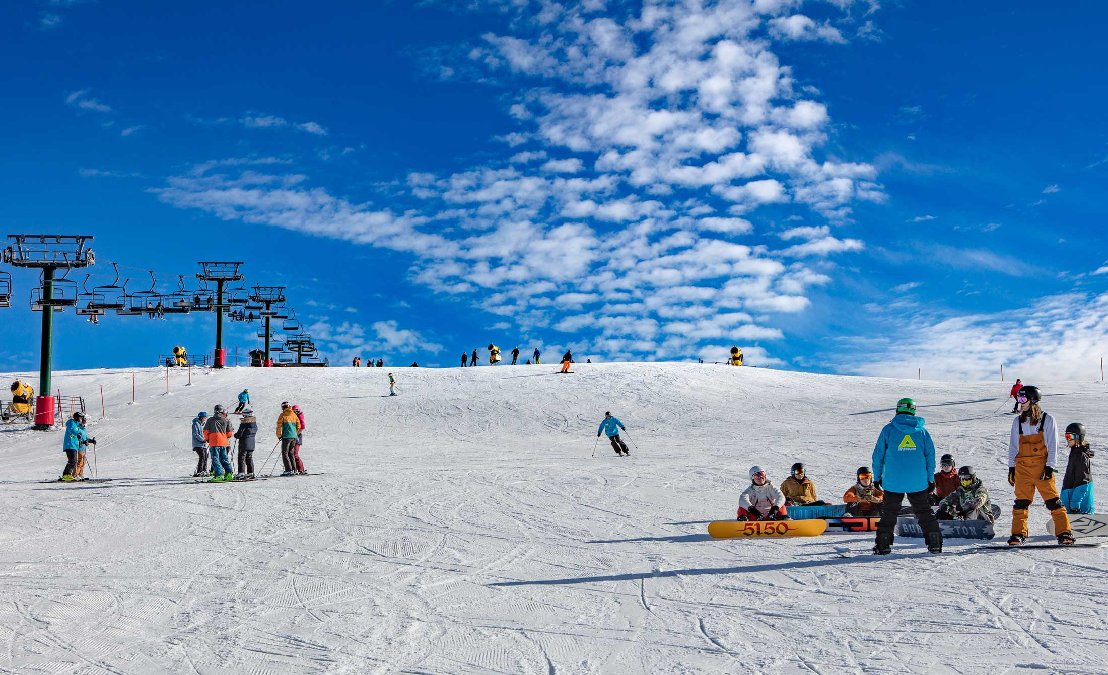 Families skiing and snowboarding on Mt Hotham on a bright, sunny, winters day